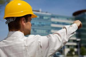 Architekt im Helm zeigt auf die Baustelle foto