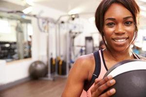 Porträt einer lächelnden Frau, die einen Medizinball hält foto
