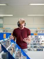 Kerl, der Musik im CD-Laden hört foto