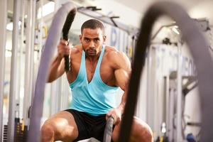 junger Mann, der mit Kampfseilen in einem Fitnessstudio trainiert foto