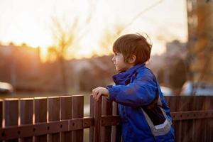 entzückender kleiner Junge, der neben einem Zaun steht foto
