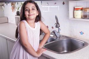 schönes Mädchen in der schönen weißen Küche (Serie) foto