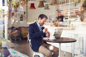 junger Mann, der in einem Café sitzt und ein Dessert isst foto