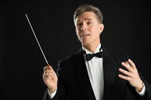 Musikdirigent, der wegschaut, während er mit seinem Schlagstock Regie führt foto