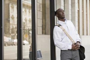 Mann wartet an der Bushaltestelle