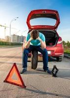 trauriger Mann, der auf Reserverad nahe gebrochenem Auto sitzt foto