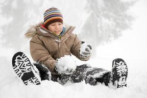 Junge sitzt im Schnee foto