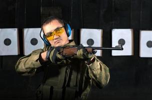 Mann schießt mit Gewehr foto