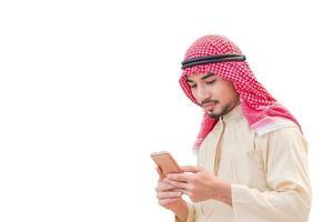 Porträt des jungen Arabers, der das Smartphone hält und auf mobilen Bildschirm auf isoliertem weißem Hintergrund schaut foto