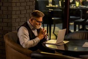 Seitenansicht des nachdenklichen älteren Geschäftsmannes, der Laptop-Bildschirm im Café betrachtet foto