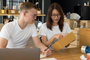 Start-up Kleinunternehmer am Arbeitsplatz arbeiten. freiberuflicher Verkäufer von Männern und Frauen prüfen die Produktbestellung auf Lieferung. Online-Verkauf, E-Commerce, Versandkonzept foto