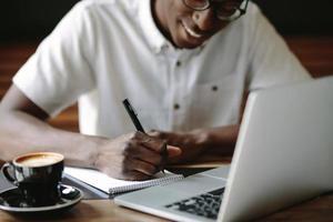 Mann, der Notizen schreibt, die an einem Café mit einem Laptop auf dem Tisch sitzen
