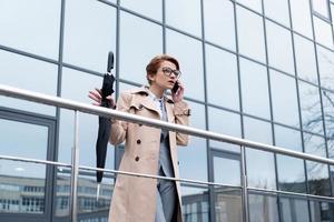 Geschäftsfrau mit Regenschirm, der auf Smartphone auf Straße spricht foto