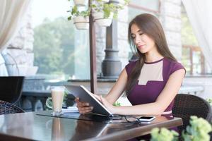 junge Frau, die mit digitaler Tablette im Café arbeitet foto