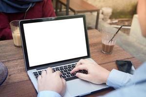 Südostasiatischer junger professioneller Geschäftsmann hat ein Treffen und verwendet modernen Laptop im Freiencafé foto