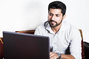 Mann sitzt in Freizeitkleidung am Computer. foto