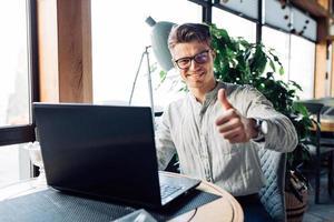 glücklicher Mann, der einen Daumen nach oben zeigt, während er im Café mit Laptop ruht foto