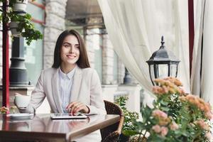 junge Geschäftsfrau, die draußen Kaffee trinkt foto