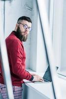 Seitenansicht des stilvollen Geschäftsmannes, der Kamera beim Tippen auf Laptop betrachtet foto