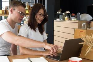 Startup-Kleinunternehmer, der mit Computer am Arbeitsplatz arbeitet. freiberuflicher Verkäufer von Männern und Frauen prüfen die Produktbestellung auf Lieferung. Online-Verkauf, E-Commerce, Versandkonzept foto