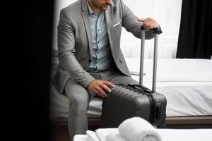 eleganter Geschäftsmann, der in seinem Hotelzimmer sitzt foto