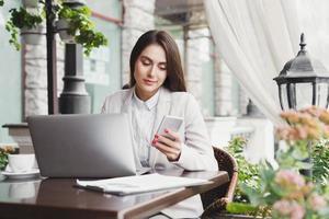 SMS-Nachricht der jungen Geschäftsfrau während des Mittagessens foto