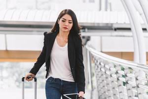 glückliche erfolgreiche Geschäftsfrau, die mit Gepäck geht foto