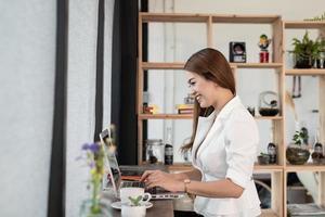schöne junge Frau, die ein asiatischer Geschäftsmann ist, der glücklich lächelt, mit einem Laptop in einem Café des Cafés arbeitend. foto
