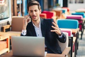 junger Unternehmer, der an Laptop und Telefon arbeitet foto