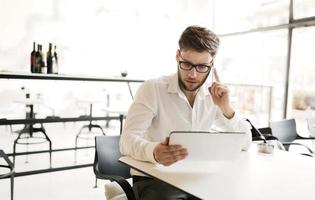 selbstbewusster beschäftigter Geschäftsmann, der an Tablette arbeitet foto