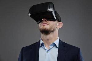 Mann in einem Anzug mit Virtual-Reality-Brille auf dem Kopf.