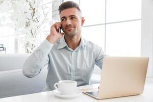 schöner Geschäftsmann, der mit Laptop arbeitet und im Café telefoniert