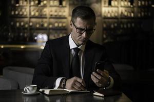 Porträt des ernsthaften gutaussehenden eleganten kaukasischen Geschäftsmannes, der am modernen Restaurant sitzt, sein Smartphone prüft und die Notizen in sein Notizbuch schreibt