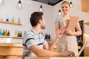 freudiger hungriger Mann, der die Kellnerin ansieht foto