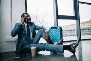 Geschäftsmann sitzt auf dem Boden und spricht per Smartphone foto