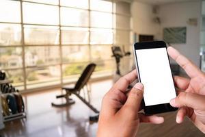 Hand des jungen Mannes, der Smartphone im Fitnessstudio zum Fitness-Telefon-Fitness-Übungskonzept hält