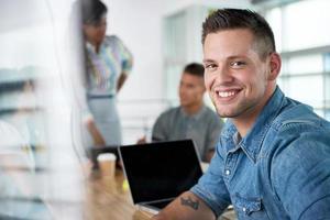 Bild eines erfolgreichen zufälligen Geschäftsmannes, der Laptop während verwendet foto