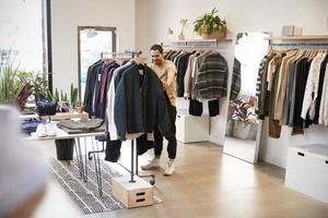 junger spanischer Mann, der durch Kleidung in einem Geschäft stöbert foto
