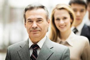 glückliches lächelndes Geschäftsteam, das in der Reihe im Büro steht foto