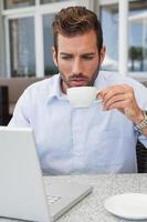 schöner Geschäftsmann, der mit Laptop arbeitet, der Kaffee trinkt foto