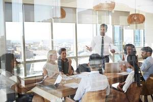 Geschäftsmann führt Treffen um Tisch durch Tür geschossen foto