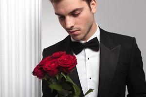 eleganter Geschäftsmann, der einen roten Rosenstrauß betrachtet foto