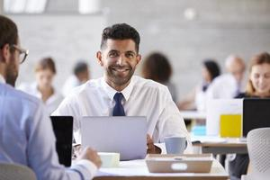 Porträt des Geschäftsmannes, der am Laptop im geschäftigen Büro arbeitet foto