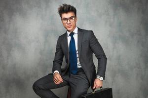 sitzender junger Geschäftsmann mit Brille, die eine Aktentasche hält foto