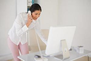 Gelegenheitsgeschäftsfrau, die das Telefon beantwortet foto