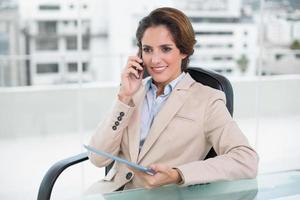 lächelnde Geschäftsfrau, die mit Smartphone anruft foto