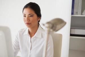 Gelegenheitsgeschäftsfrau, die an ihrem Schreibtisch arbeitet foto