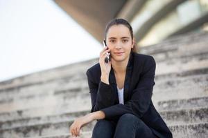 selbstbewusste Geschäftsfrau, die im Freien am Telefon verhandelt foto