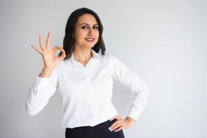 lächelnde hübsche Geschäftsfrau, die ok Zeichen zeigt foto