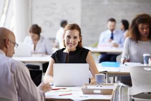 Porträt der Geschäftsfrau, die am Laptop im geschäftigen Büro arbeitet foto
